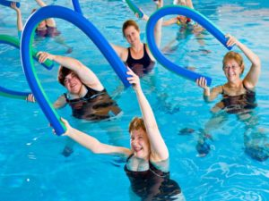 Women with water aerobics noodles